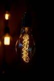 垂悬在一根长的导线的爱迪生电灯泡 舒适温暖的黄灯 减速火箭 免版税库存图片