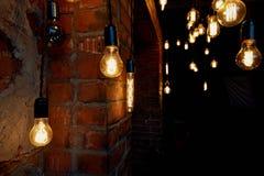 垂悬在一根长的导线的爱迪生电灯泡 舒适温暖的黄灯 减速火箭 库存照片