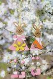 垂悬在一棵开花的樱桃树的分支的装饰复活节兔子 图库摄影