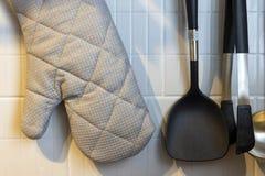 垂悬在不锈钢路轨的浅灰色的烤箱手套 图库摄影