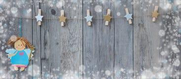 垂悬在与一点圣诞节神仙的绳索和雪的装饰的晒衣夹在fraime附近 免版税库存照片