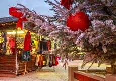 垂悬在与圣诞节市场瑞士山中的牧人小屋的一棵多雪的树的圣诞节球的特写镜头在backgr 免版税图库摄影
