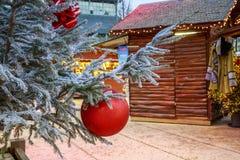 垂悬在与圣诞节市场瑞士山中的牧人小屋的一棵多雪的树的圣诞节球的特写镜头在backgr 免版税库存图片