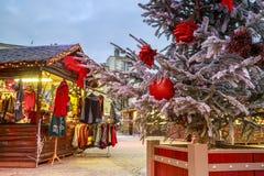 垂悬在与圣诞节市场瑞士山中的牧人小屋的一棵多雪的树的圣诞节球的特写镜头在backgr 库存照片