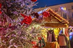 垂悬在与圣诞节市场瑞士山中的牧人小屋的一棵多雪的树的圣诞节球的特写镜头在backgr 库存图片
