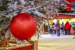 垂悬在与圣诞节市场瑞士山中的牧人小屋的一棵多雪的树的圣诞节球的特写镜头在backgr 免版税库存照片