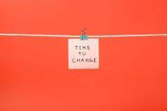 垂悬在与文本时间的串的桃红色纸笔记改变 免版税库存图片
