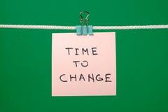 垂悬在与文本时间的串的桃红色纸笔记改变 库存照片