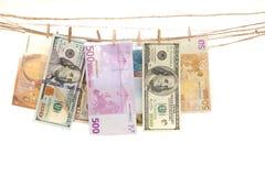 垂悬在与晒衣夹的一条绳索的欧元和dolar钞票 免版税库存图片