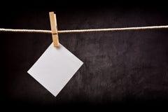 垂悬在与晒衣夹的绳索的空白的便条纸 库存照片