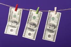垂悬在与木夹子的晒衣绳的一百美元在蓝色背景 免版税库存照片