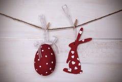 垂悬在与框架的线的一个红色复活节兔子和复活节彩蛋 免版税库存照片