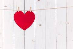 垂悬在与空间的白色木头的空白的红色心脏华伦泰的a 库存图片