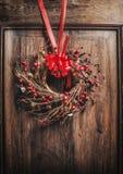 垂悬在与红色丝带和莓果的木门的手工制造圣诞节花圈 免版税库存照片