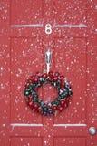 垂悬在与降雪的门的圣诞节花圈 免版税库存照片