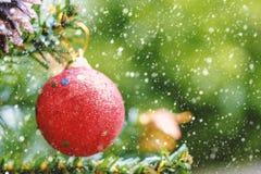 垂悬在与雪作用的树的红色圣诞节闪烁球装饰 免版税库存照片