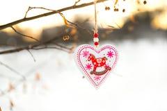 垂悬在与雪的树枝的心形的华伦泰或圣诞节装饰玩具在背景 库存照片