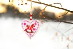 垂悬在与雪的树枝的心形的华伦泰或圣诞节装饰玩具在背景 图库摄影