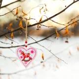 垂悬在与雪的树枝的心形的华伦泰或圣诞节装饰玩具在背景 免版税库存图片