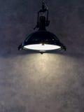 从垂悬在与Copyspace的灰色墙壁背景对输入文本的现代黑金属灯的灯罩使用作为模板 免版税库存照片