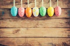 垂悬在与sp的土气木背景的五颜六色的复活节彩蛋 免版税库存图片
