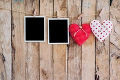垂悬在与w的晒衣绳绳索的两心脏和两张照片框架 免版税库存图片