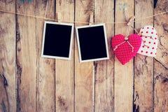 垂悬在与w的晒衣绳绳索的红色心脏和两张照片框架 库存照片