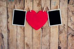 垂悬在与w的晒衣绳绳索的红色心脏和两张照片框架 免版税库存图片