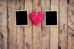 垂悬在与w的晒衣绳绳索的红色心脏和两张照片框架 图库摄影