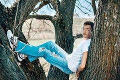 垂悬在两棵树之间的一个年轻人 库存照片