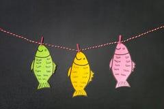 垂悬在串的纸鱼在黑板附近 免版税库存照片