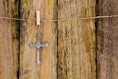 垂悬在串的银色金属耶稣受难象反对土气木ba 库存图片
