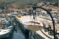 垂悬在九头蛇, Gr海岛的船坞的链子的小船  免版税库存图片