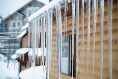 垂悬在乡间别墅屋顶的冬天冰柱 免版税库存图片