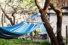 垂悬在乡间别墅的庭院里的蓝色吊床 免版税库存图片