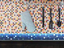 垂悬在五颜六色的马赛克的厨房器物围住瓦片 免版税库存照片