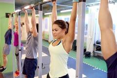 垂悬在健身房的单杠的人 库存图片