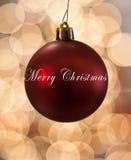 垂悬在光前面的唯一红色圣诞节装饰品 图库摄影