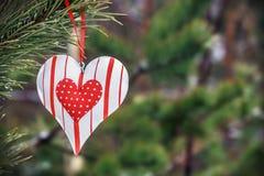 垂悬在冬天树的玩具心脏 免版税库存照片