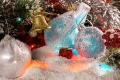 垂悬在分支的金黄圣诞节铃声与圣诞节装饰一起 多彩多姿的光,发光,精采闪亮金属片 免版税库存照片