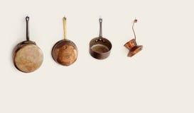 垂悬在勾子的减速火箭的厨房器物 老牌辅助部件上铜平底深锅滤锅咖啡壶 复制空间 库存照片