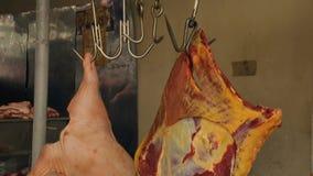 垂悬在勾子的新鲜的生肉在室外市场,肉店,质量管理上 影视素材