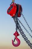 垂悬在卷轴链子和蓝天日落ba的红色工业勾子 图库摄影