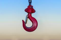 垂悬在卷轴链子和蓝天日落ba的红色工业勾子 免版税库存图片