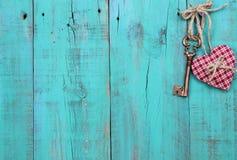 垂悬在古色古香的小野鸭蓝色木门的格子花呢披肩心脏和古铜色万能钥匙 免版税图库摄影