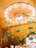 垂悬在古色古香的枝形吊灯的绿皮书天鹅 库存图片
