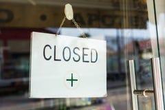 垂悬在商店窗口里的闭合的标志 免版税图库摄影