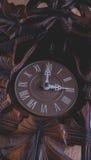 垂悬在土气木墙壁上的布谷鸟钟 库存照片