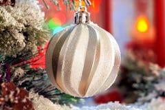 垂悬在圣诞树的一个积雪的分支的白色发光的球以红色灯笼和色的光为背景 库存图片