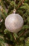 垂悬在圣诞树的银色圣诞节球 免版税图库摄影